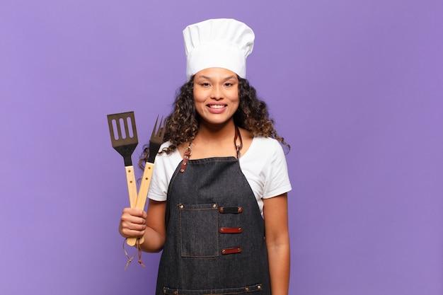 Молодая латиноамериканская женщина выглядит счастливой и приятно удивленной, взволнованной, с очарованным и шокированным выражением лица. концепция шеф-повара барбекю