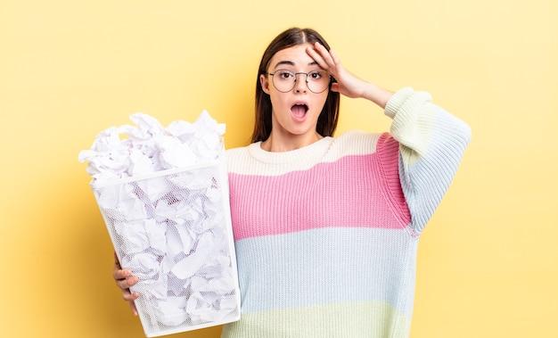 Молодая латиноамериканская женщина выглядит счастливой, удивленной и удивленной. отказ от мусора