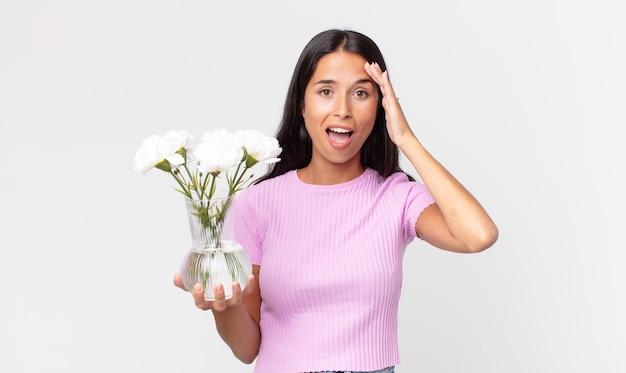 장식용 꽃을 들고 행복하고 놀라고 놀란 젊은 히스패닉 여성