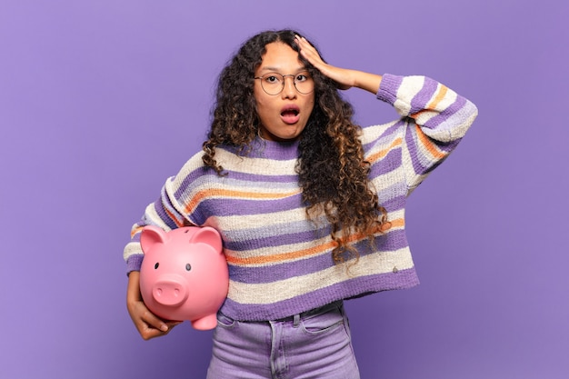 Young hispanic woman looking happy, astonished and surprised, smiling and realizing amazing and incredible good news. piggy bank concept