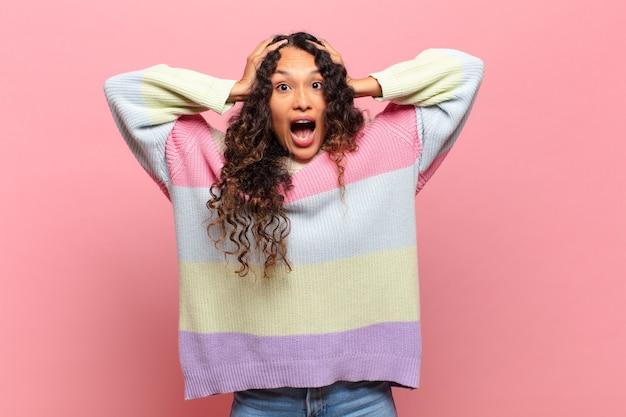 Молодая латиноамериканская женщина выглядит счастливой, беззаботной, дружелюбной и расслабленной, наслаждаясь жизнью и успехом, с позитивным настроем