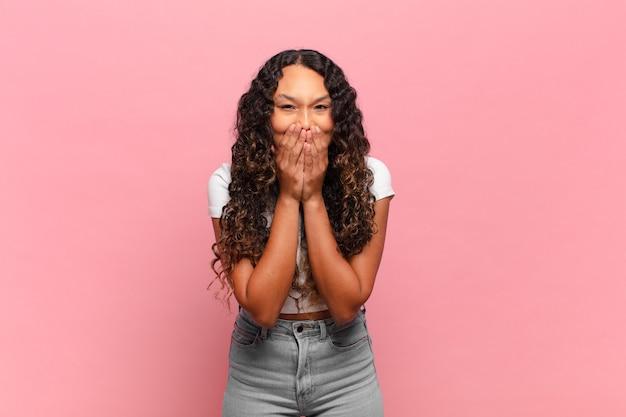 Молодая латиноамериканская женщина выглядит счастливой, веселой, удачливой и удивленной, прикрывая рот обеими руками