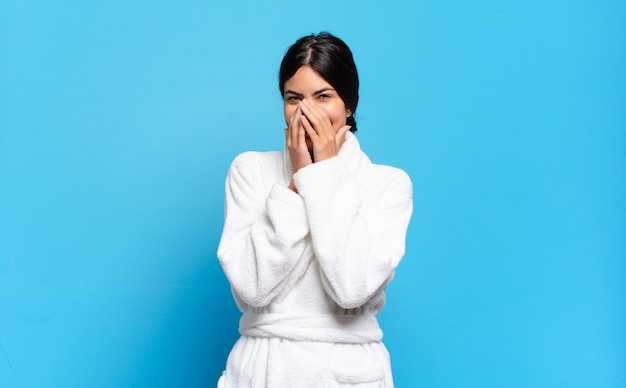 Young hispanic woman looking happy, cheerful, lucky and surprised covering mouth with both hands. bathrobe concept