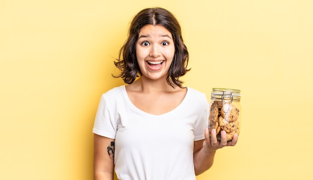 Young hispanic woman looking happy and pleasantly surprised. cookies bottle concept