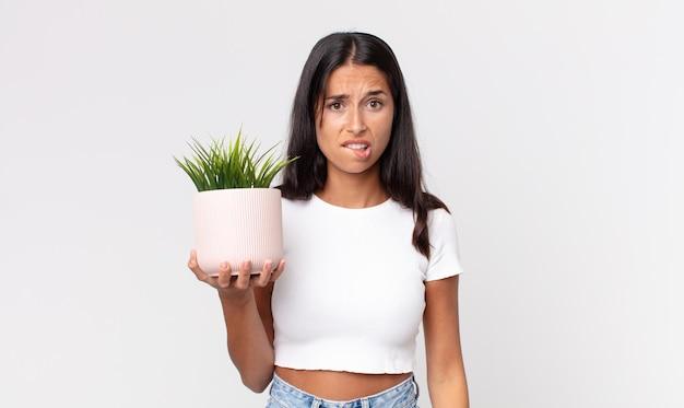 어리둥절하고 혼란스러워 보이는 젊은 히스패닉 여성이 장식용 집 식물을 들고 있다