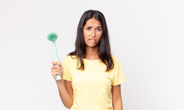 困惑して混乱しているように見え、皿掃除ブラシを持っている若いヒスパニック系女性