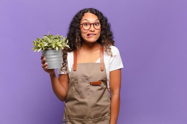 Молодая латиноамериканка выглядела озадаченной и сбитой с толку, нервно закусив губу, не зная ответа на проблему. концепция садовника