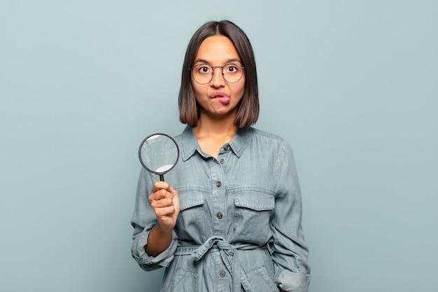 의아해하고 혼란스러워 보이는 젊은 히스패닉 여성, 문제에 대한 답을 모르는 긴장된 몸짓으로 입술을 물고
