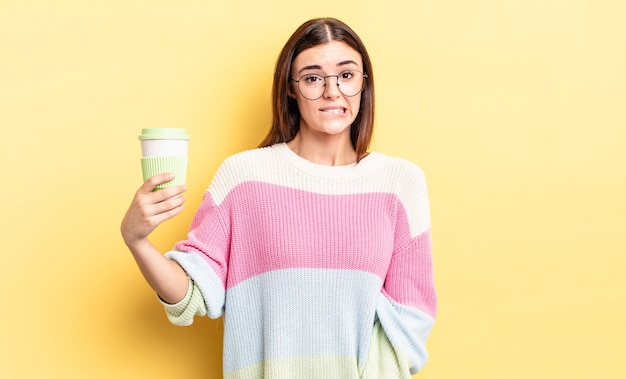 困惑して混乱しているように見える若いヒスパニック系女性。コーヒーのコンセプトを奪う