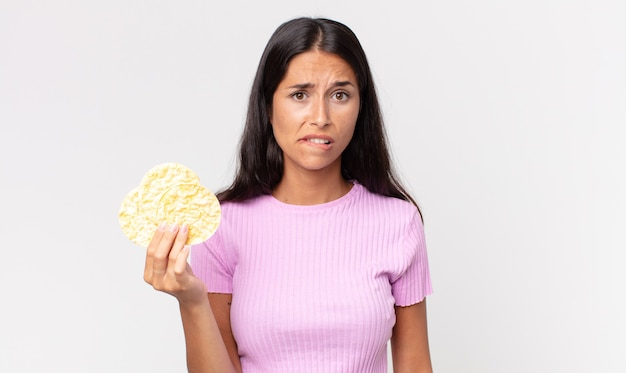 Young hispanic woman looking puzzled and confused and holding a rice cookie. diet concept