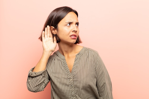 ヒスパニック系の若い女性は、真剣で好奇心をそそり、秘密の会話やゴシップを聞こうとしている
