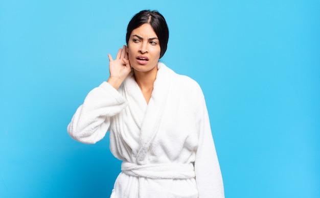 Молодая латиноамериканская женщина выглядит серьезной и любопытной