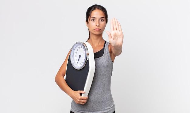 젊은 히스패닉계 여성이 손바닥을 펴고 중지 제스처를 하고 체중계를 들고 진지하게 보입니다. 다이어트 개념
