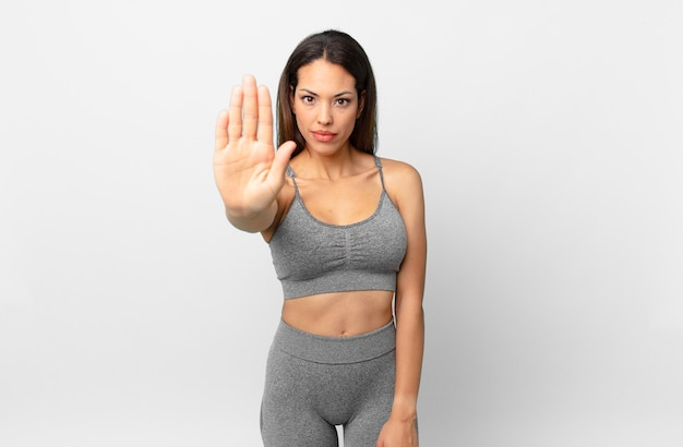 Young hispanic woman looking serious showing open palm making stop gesture. fitness concept