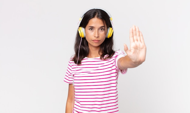 Young hispanic woman looking serious showing open palm making stop gesture listening music with headphones