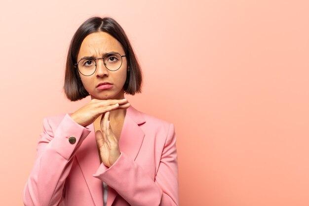 Молодая латиноамериканская женщина выглядит серьезной, суровой, сердитой и недовольной, делая знак тайм-аута
