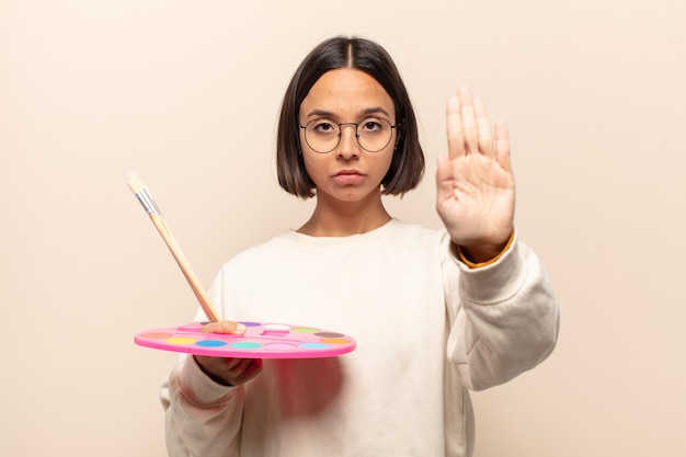 Young hispanic woman looking serious, stern, angry and displeased, making time out sign