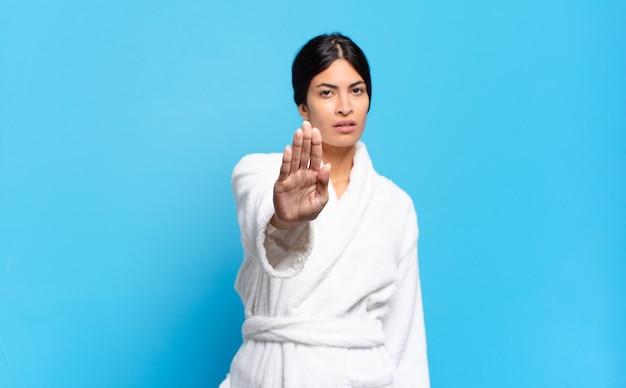 若いヒスパニック系の女性は、真面目で、厳しく、不機嫌で、怒っているように見え、手のひらを開いてジェスチャーを止めています。バスローブのコンセプト