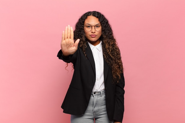 若いヒスパニック系の女性は、真面目で、厳しく、不機嫌で、怒っているように見え、手のひらを開いてジェスチャーを止めています。ビジネスコンセプト