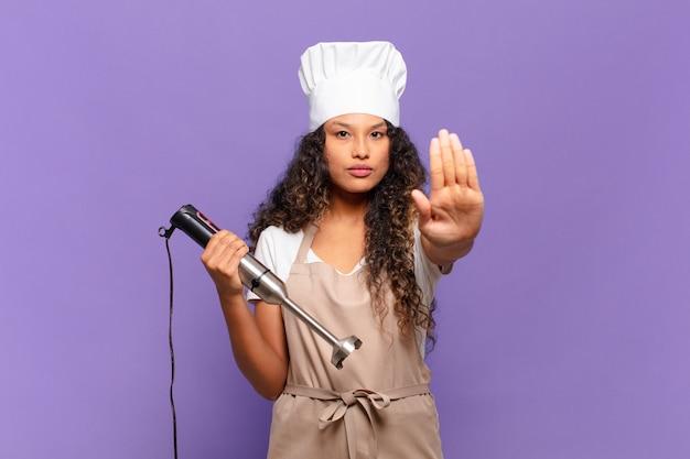 Молодая латиноамериканская женщина, выглядящая серьезной, суровой, недовольной и сердитой, показывает открытую ладонь, делая стоп-жест. концепция шеф-повара