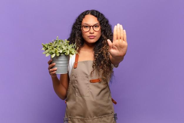 Молодая латиноамериканская женщина, выглядящая серьезной, суровой, недовольной и сердитой, показывает открытую ладонь, делая стоп-жест. концепция садовода