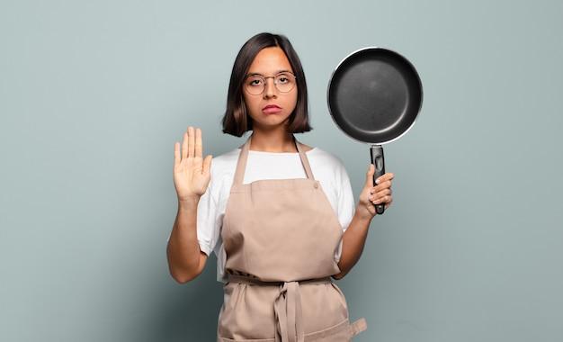 Молодая латиноамериканская женщина выглядит серьезной, строгой, недовольной и сердитой, показывая открытую ладонь, делая жест стоп