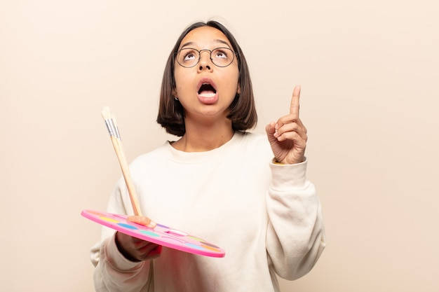 Young hispanic woman looking shocked, amazed and open mouthed, pointing upwards with both hands to copy space