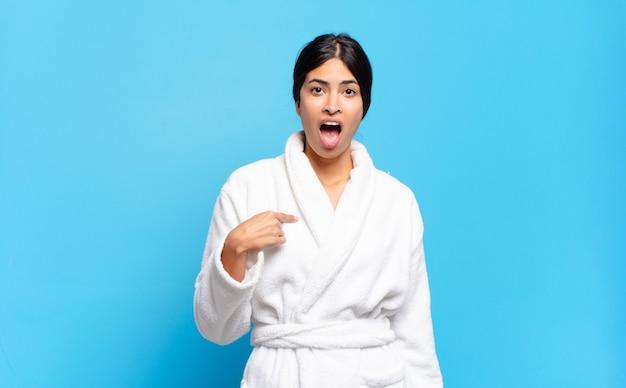 ヒスパニック系の若い女性が、口を大きく開けてショックを受け、驚いて、自分を指さしているように見えます。バスローブのコンセプト