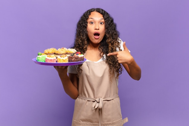 ヒスパニック系の若い女性が、口を大きく開けてショックを受け、驚いた様子で、自分を指しています。クッキングケーキのコンセプト