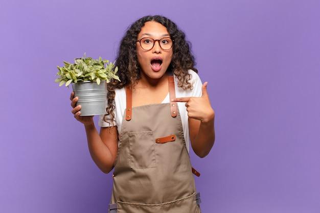 Молодая латиноамериканская женщина выглядит шокированной и удивленной с широко открытым ртом, указывая на себя. концепция садовника