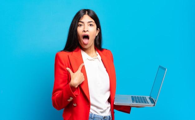 ヒスパニック系の若い女性が、口を大きく開けてショックを受け、驚いた様子で、自分を指しています。ノートパソコンのコンセプト
