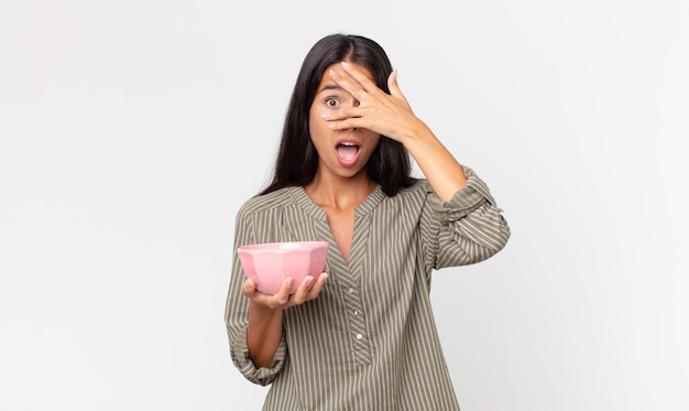 충격, 겁 또는 겁에 질려 보이는 젊은 히스패닉 여성, 손으로 얼굴을 가리고 빈 그릇이나 냄비를 들고