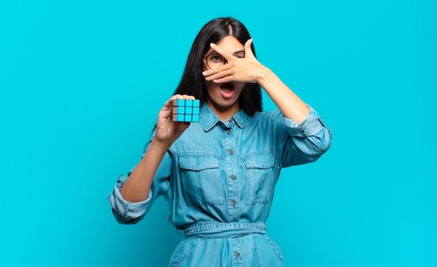 Молодая латиноамериканская женщина выглядит шокированной, напуганной или напуганной, закрывает лицо рукой и заглядывает между пальцами
