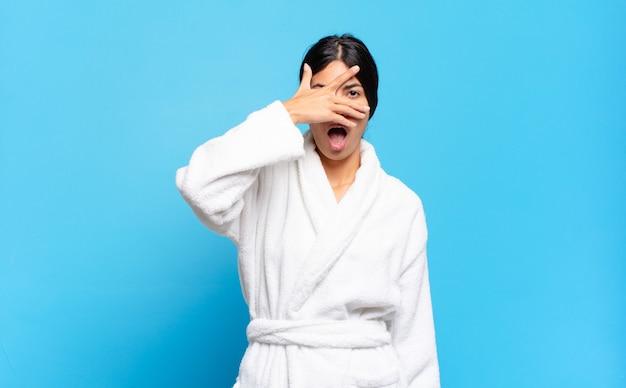 ショックを受けたり、怖がったり、恐怖を感じたり、顔を手で覆ったり、指の間をのぞいたりしている若いヒスパニック系女性。