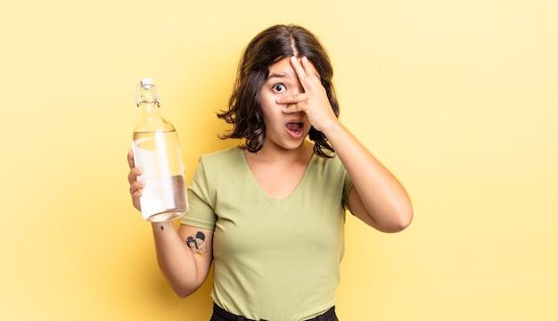 ショックを受けたり、怖がったり、恐怖を感じたりして、顔を手で覆っている若いヒスパニック系女性。ウォーターボトルのコンセプト