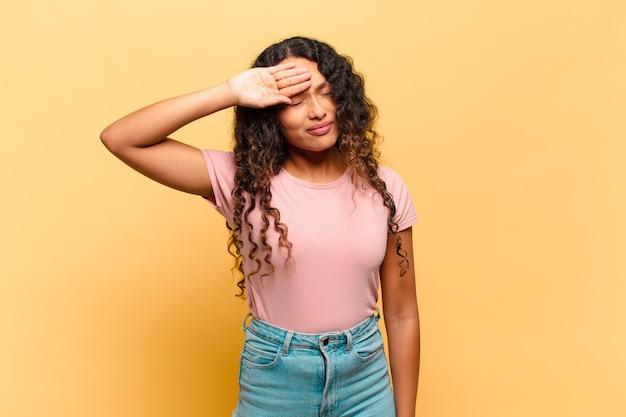 ストレス、疲れ、欲求不満を見て、額から汗を乾かし、絶望的で疲れ果てていると感じている若いヒスパニック系女性