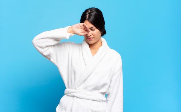 ストレス、倦怠感、欲求不満を見て、額から汗を乾かしている若いヒスパニック系女性