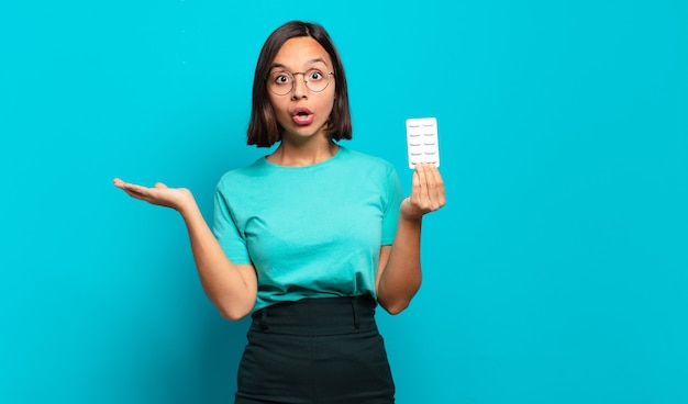 Молодая латиноамериканская женщина выглядит удивленной и шокированной, с отвисшей челюстью, держащей объект открытой рукой сбоку