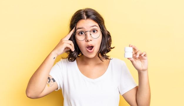 Молодая латиноамериканская женщина выглядит удивленной, осознавая новую мысль, идею или концепцию. концепция таблетки болезни