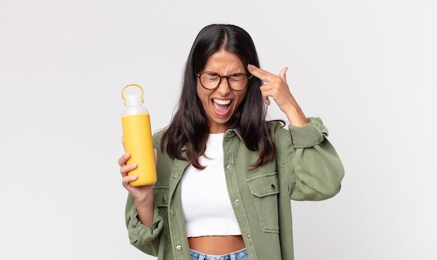 Молодая латиноамериканская женщина выглядит несчастной и подчеркнутой, жестом самоубийцы делает знак пистолета и держит термос с кофе