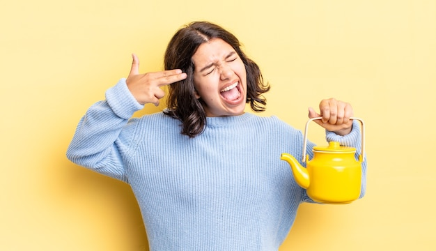 Молодая латиноамериканская женщина, выглядящая несчастной и подчеркнутой, жест самоубийства, делая знак пистолета. концепция чайника