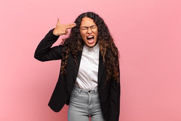 불행하고 스트레스를 받는 젊은 히스패닉 여성, 머리를 가리키는 손으로 총 기호를 만드는 자살 제스처. 비즈니스 개념