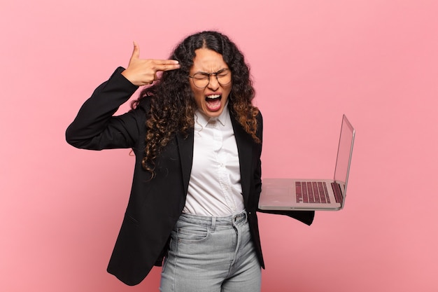 Молодая латиноамериканская женщина, выглядящая несчастной и подчеркнутой, жест самоубийства делает знак пистолет рукой, указывая на голову. концепция ноутбука