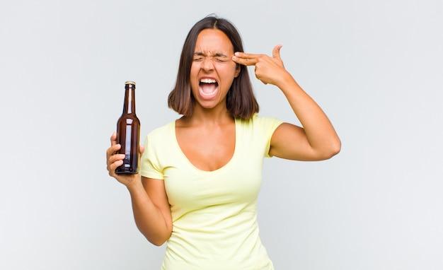 불행 하 고 스트레스를 찾고 젊은 히스패닉 여자, 머리를 가리키는 손으로 총 기호를 만드는 자살 제스처