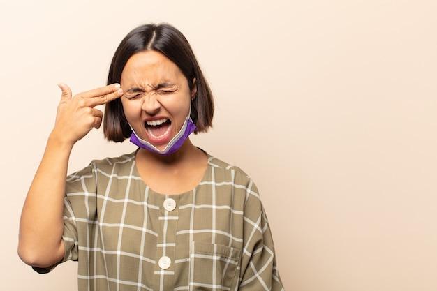 不幸でストレスを感じている若いヒスパニック系女性、手で銃のサインを作る自殺ジェスチャー、頭を指して
