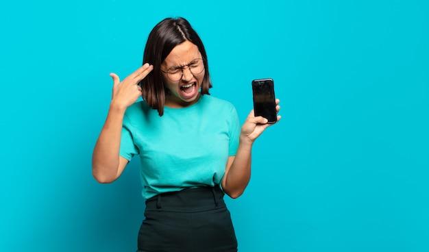 Молодая латиноамериканская женщина выглядит несчастной и подчеркнутой, жест самоубийства делает знак пистолет рукой, указывая на голову