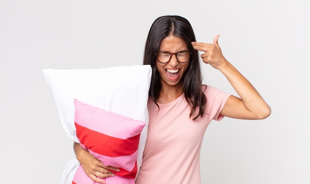 Young hispanic woman looking unhappy and stressed, suicide gesture making gun sign wearing pajamas and holding a pillow