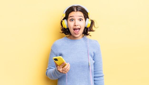 非常にショックを受けたり驚いたりしている若いヒスパニック系女性。ヘッドフォンとスマートフォンのコンセプト