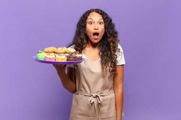 젊은 히스패닉 여자는 매우 충격을 받거나 놀란 표정으로 입을 벌리고 와우를 쳐다보고 있습니다. 요리 케이크 개념
