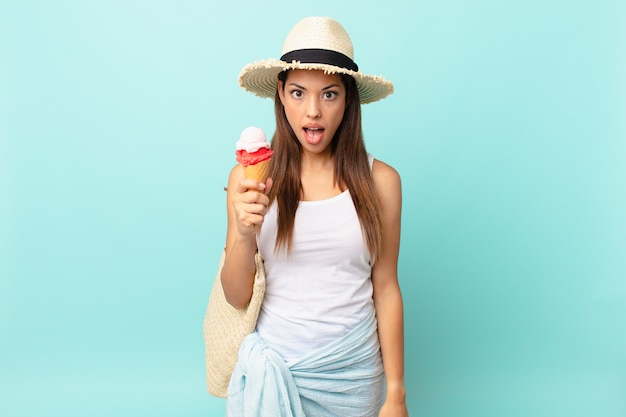 Young hispanic woman looking very shocked or surprised and holding an ice cream. sumer concept